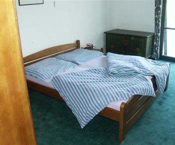 Pokoj s manželskou postelí a komodou