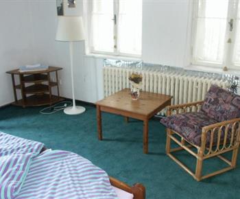 Pokoj s lůžky, křeslem a stolkem