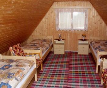 Podkrovní ložnice s lůžky, nočními stolky a lampičkami