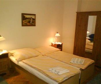 Ložnice s lůžky , nočními stolky, lampičkami a skříní