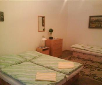 Ložnice B s lůžky, nočními stolky, lampičkami a skříní