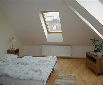 Ložnice B v podkroví s lůžky, nočními stolky, lampičkami a skříní