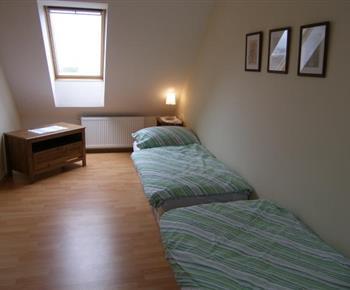 Ložnice C v podkroví s lůžky, nočními stolky, lampičkami a skříní