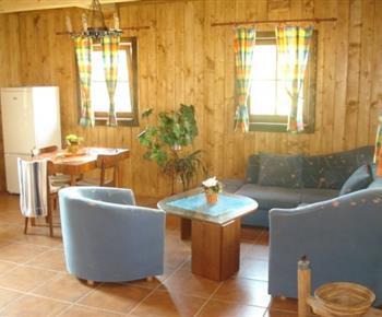 Společenská místnost se sedací soupravou, stolkem a televizorem