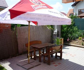 Venkovní posezení pod slunečníkem u zahradního grilu