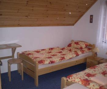Podkrovní pokoj s lůžky, nočními stolky a lympičkami