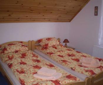 Ložnice v podkroví s lůžky, nočními stolky a lampičkami