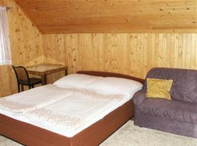 Podkrovní pokoj s lůžky, pohovkou, stolem a židlí