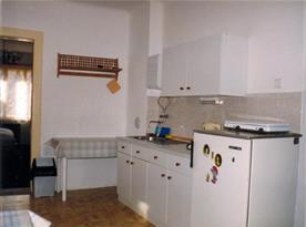 Kuchyně se sporákem, lednicí, varnou konvicí, stolem a židlemi