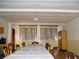 Společenská místnost se stoly, židlemi a televizí