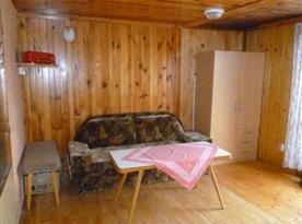 Obývací pokoj s rohovou sedačkou, stolem, židlemi a televizí