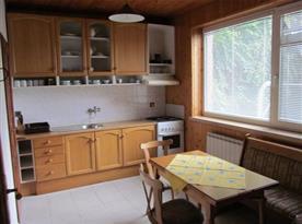 Kuchyně se sporákem, ledničkou a jídelním koutem