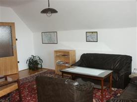 Obývací hala se sedací soupravou, stolkem, televizí a vstupem na balkón
