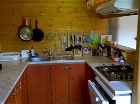Kuchyňský kout se sporákem, lednicí, mikrovlnou troubou a rychlovarnou konvicí