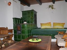 Společenská místnost s posezením a kachlovými kamny