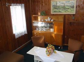 Společenská místnost s pohovkou, stolkem a televizí se satelitem