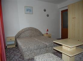 Ložnice s manželskou postelí, nočními stolky a skříní