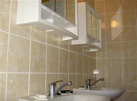 Koupelna se dvěma umyvadly a skříňkami