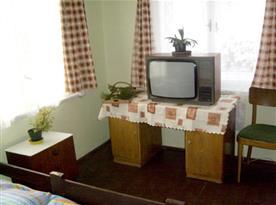 Ložnice A s lůžky, skříní, televizí, nočním stolkem a židlí