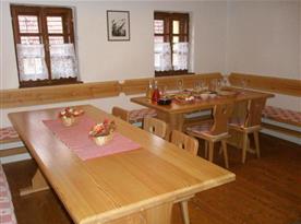 Společenská místnost se stoly, židlemi a lavicemi