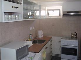 Kuchyně s linkou, sporákem, troubou, lednicí, mikrovlnou troubou a rychlovarnou konvicí