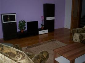 Obývací pokoj se sedací soupravou a televizí