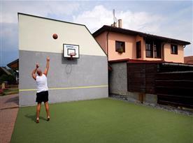 Tenisová zeď s baketbalovým košem na pozemku u objektu
