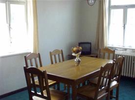 Pokoj B se stolem,  židlemi a televizí