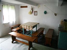 Pohled na letní kuchyňku s posezením a kamny na tuhá paliva